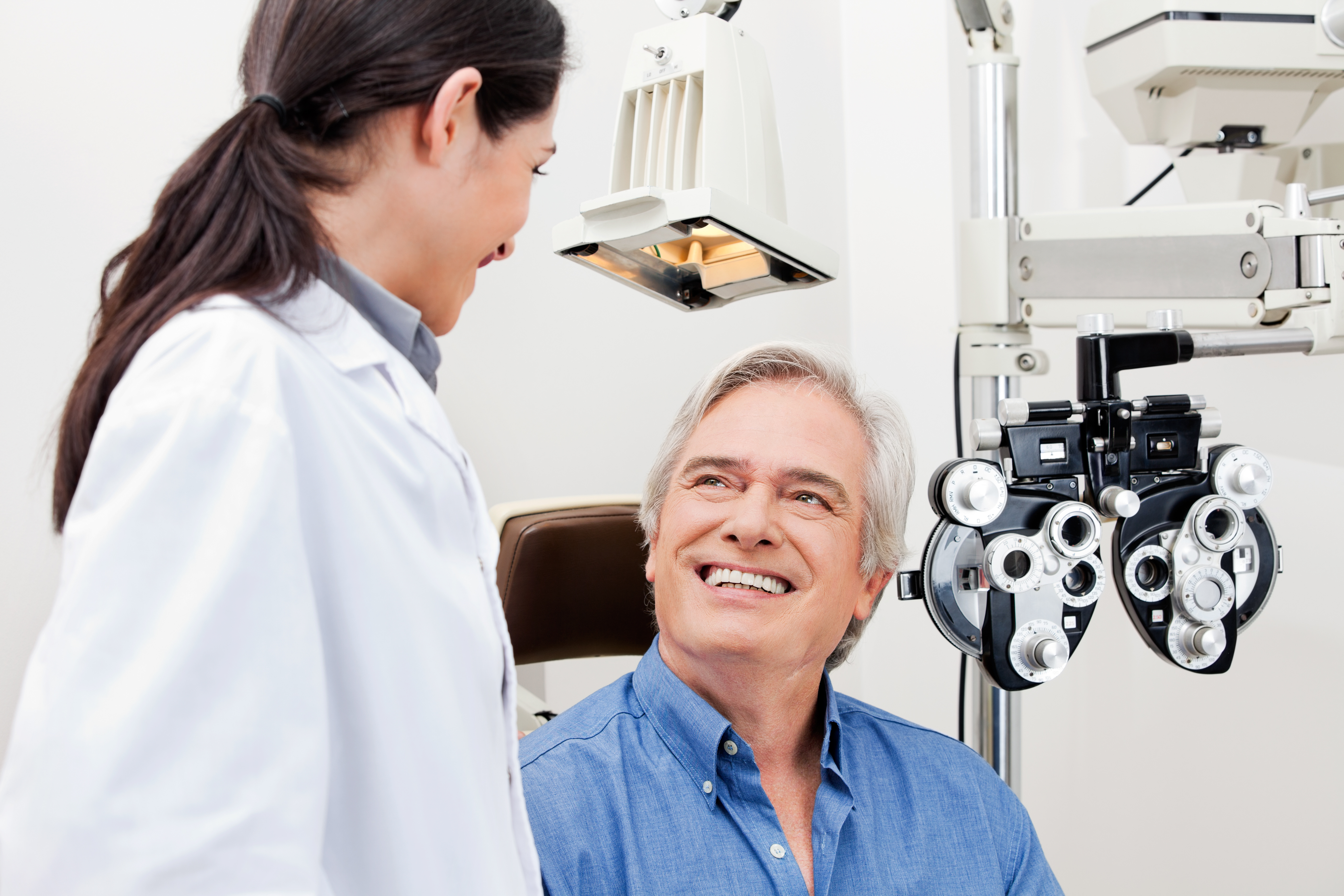 woman eye doctor looking down and smiling at sitting elderly patient