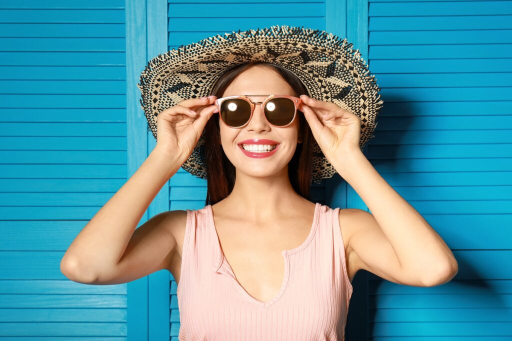 Beautiful woman wearing sunglasses and hat near blue wooden