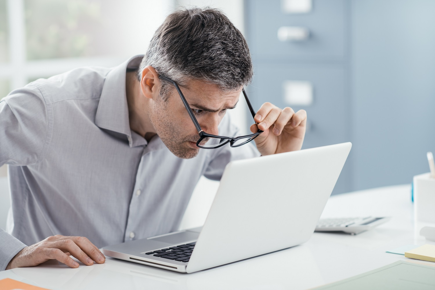 Businessman working at office desk, he is staring at the laptop screen
