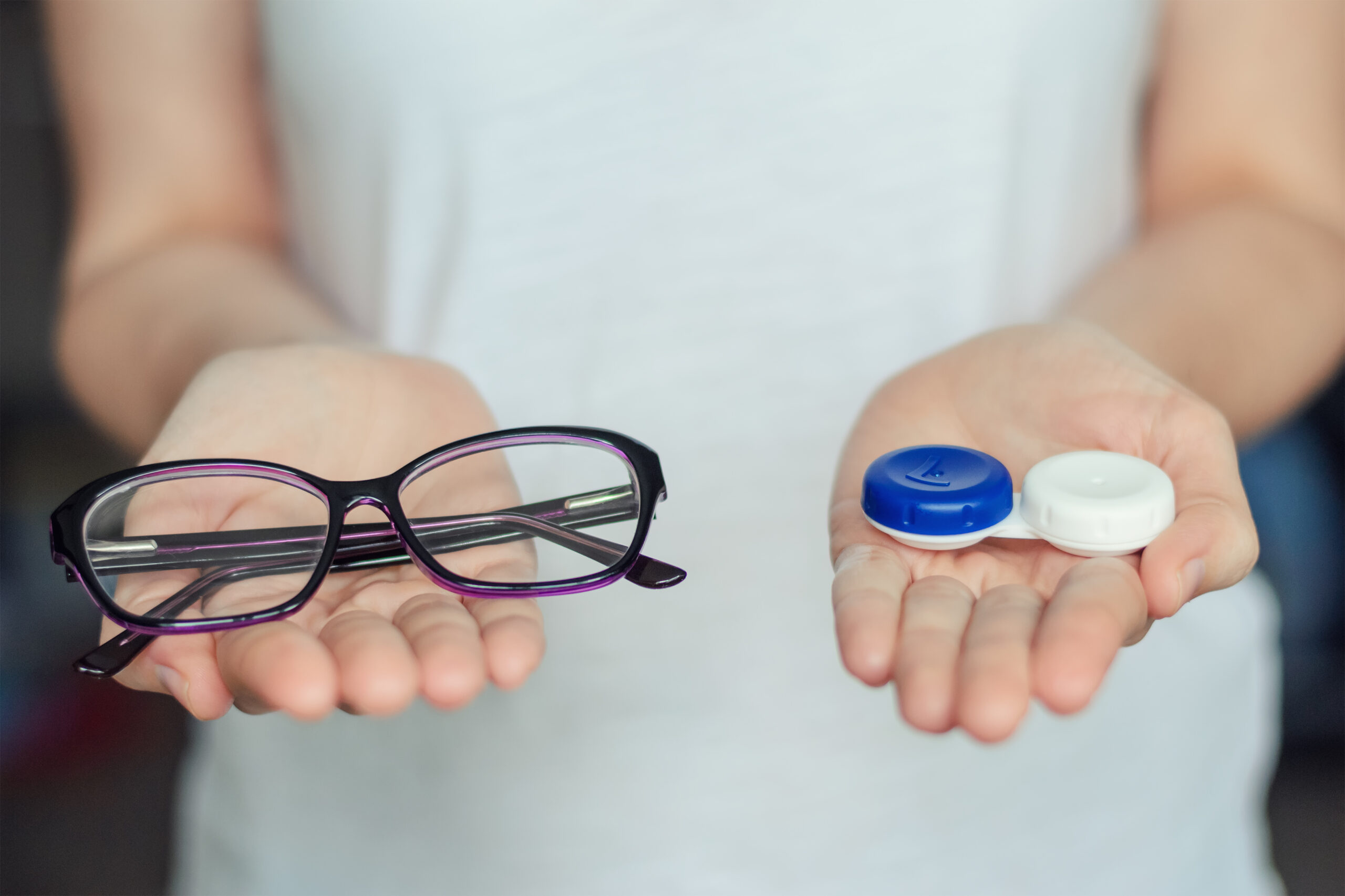 woman hold contact lenses and glasses in hands