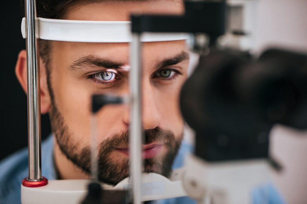 Handsome young man is checking the eye vision in modern ophthalmology clinic