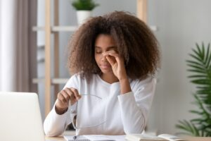 African teen girl rubbing eyes tired from computer holding glasses
