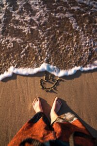 women feet on sand with smiley doodle