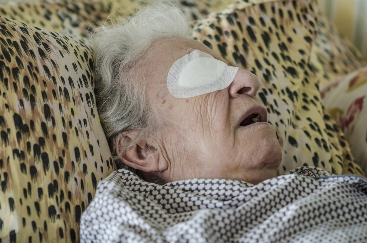 an old person with eye bandage after cataract operation