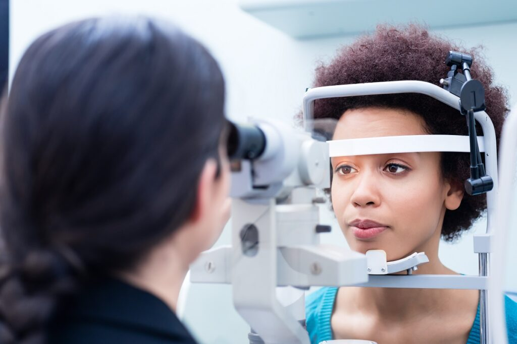Optician measuring women eyes with refractometer
