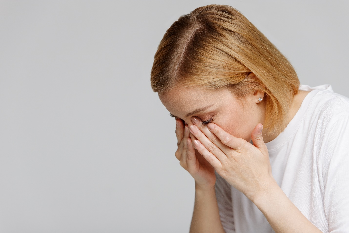 Young woman rubbing her swollen eyes due to pollen