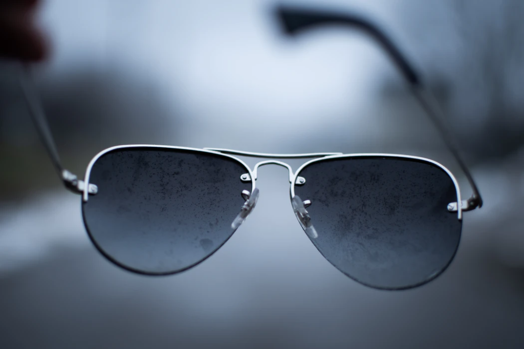 man holding sunglasses with water on them on a rainy day