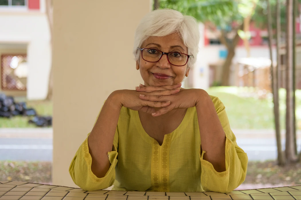 smiling old woman sitting front of table