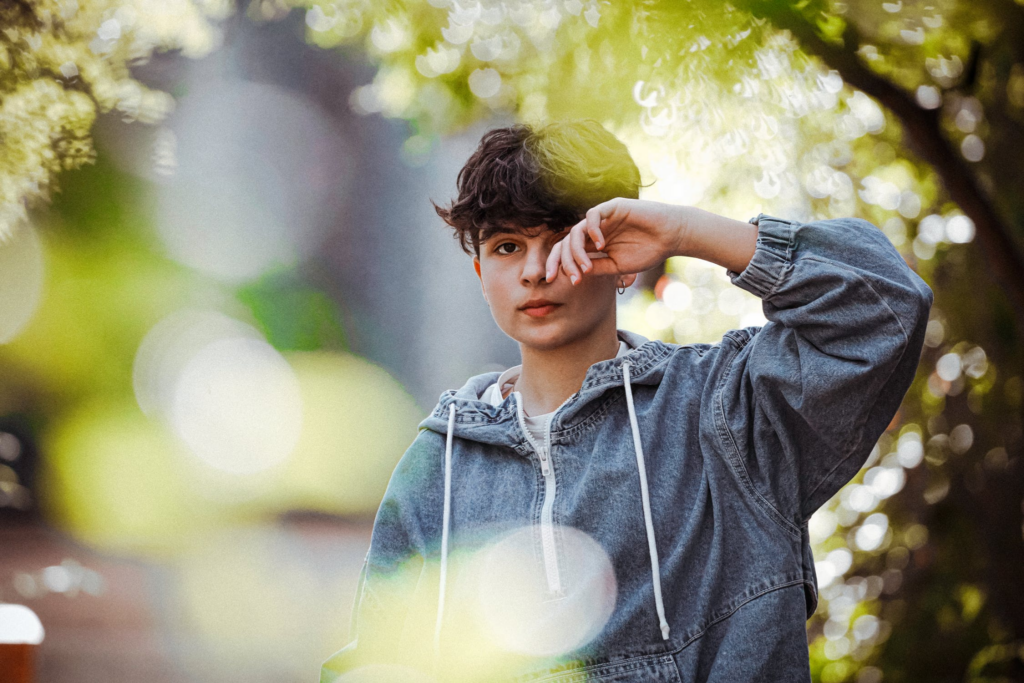 Teenager rubbing eye while standing near green trees in park